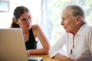 Beratungssituation zwischen junger und alter Person am Laptop