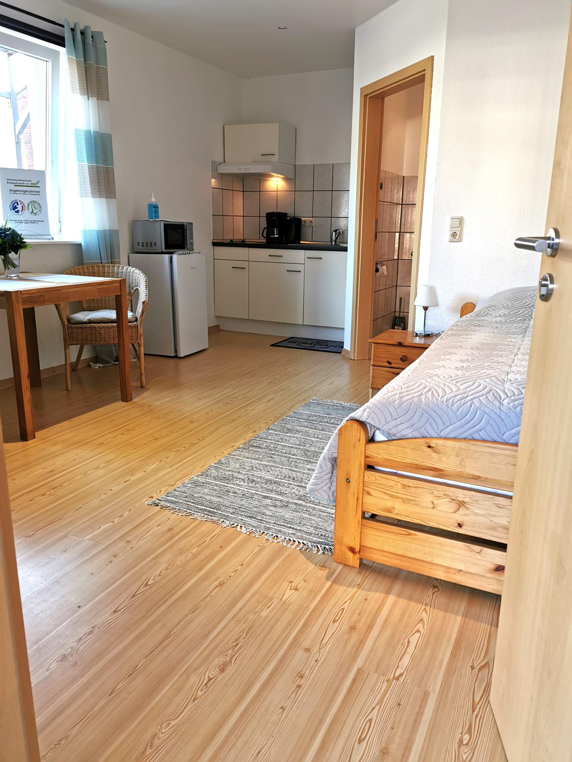 Blick auf Bett und Küchenzeile