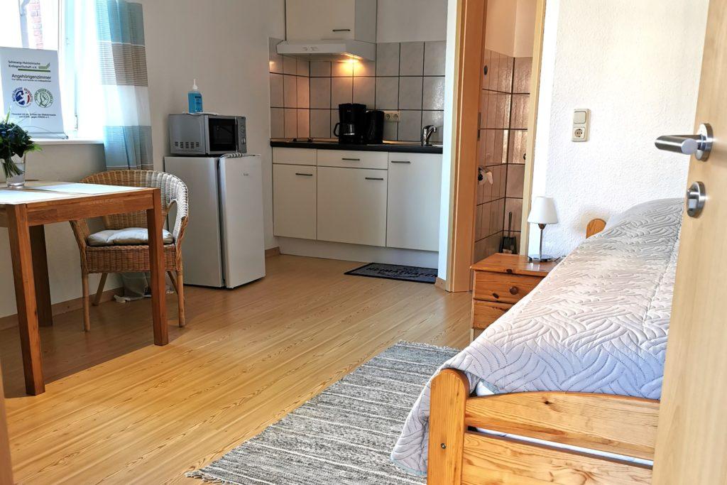 Blick ins Zimmer mit Bett und Kochnische